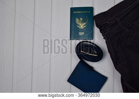 Passport, Wallet, Buckle And Gray Jeans On Wooden Table. Traveling Concept