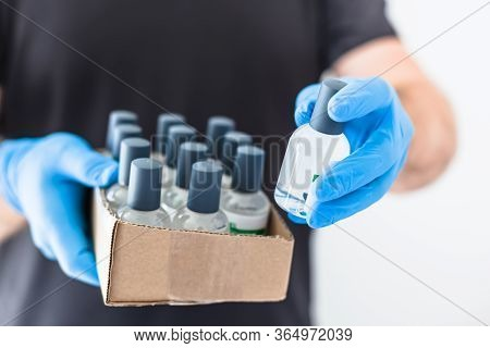 Hand Sanitizer Hygiene Alcohol Gel Bottles In Hands Of Man Wearing Latex Medical Gloves And Protecti