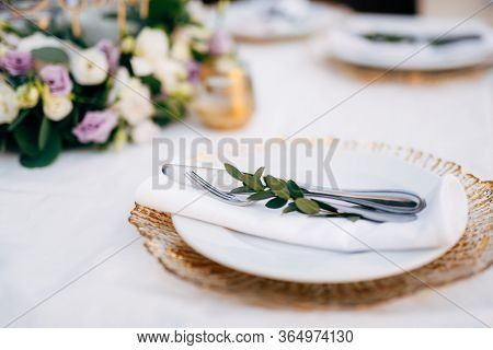 Wedding Dinner Table Reception. White Plate On Top Of A Wildcard With Golden Edges. In A White Plate