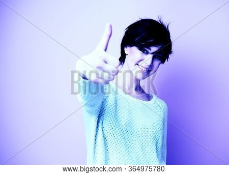Female portrait with positive expressions and thumb up. Beautiful young woman happy and excited expressing winning gesture. Successful and celebrating victory, triumphant, image toned in acid shades