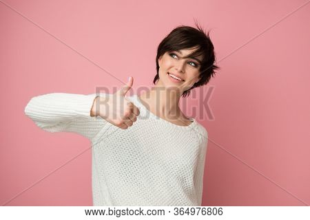 Female portrait with positive expressions and thumb up looking left at copy space. Beautiful young woman happy and excited expressing winning gesture. Successful and celebrating victory, triumphant