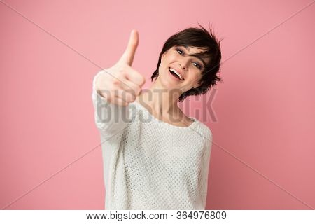 Female portrait with positive expressions and thumb up looking at camera. Beautiful young woman happy and excited expressing winning gesture. Successful and celebrating victory, triumphant, over pink