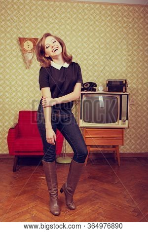 Young smiling ecstatic woman looking at camera and happy smiling in room with vintage wallpaper and interior, retro stylization 60-70s. Furniture, tv set and another technique of the mid 20th century