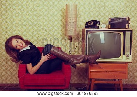 Young smiling ecstatic woman lies in a chair and looking at camera and happy smiling in room with vintage wallpaper and interior, retro stylization 60-70s. Furniture, tv set and another technique of t