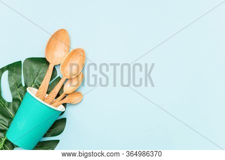 Tableware Wooden Spoons In A Paper Cup And Green Leaf On Blue Background, Top View. Zero Waste, Envi