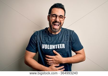 Handsome man with beard wearing t-shirt with volunteer message over white background smiling and laughing hard out loud because funny crazy joke with hands on body.