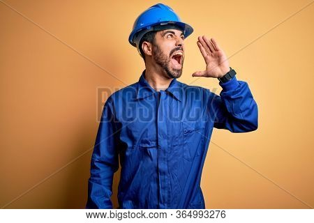 Mechanic man with beard wearing blue uniform and safety helmet over yellow background shouting and screaming loud to side with hand on mouth. Communication concept.