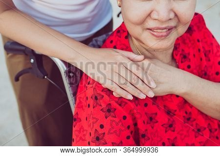 Caregiver Hands Holding To Elderly Asian Woman Sitting On Wheelchair,senior Insurance Concept