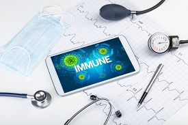 Close-up view of a tablet pc with IMMUNE inscription, microbiology concept