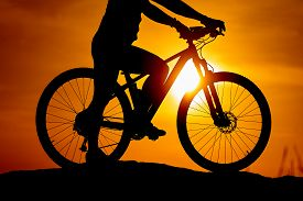 Silhouette Of A Bike With A Man On Sky Background On Sunset. Detailed Photo. Closeup