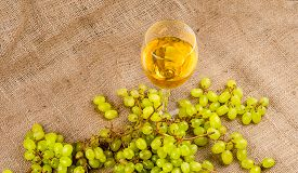 Bunch Of Grapes And A Glass Of White Wine On A Sackcloth Fabric Background