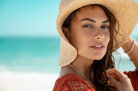 Portrait of beautiful young woman with straw hat looking at camera with copy space. Close up face of attractive tanned girl with sea in background. Fashion woman wearing lace vest enjoying summer.