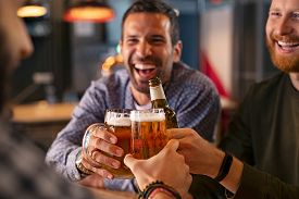 Happy mid adult friends clinking with beer mugs in pub. Three cheerful guys drinking draft beer, celebrating meeting and smiling. Laughing young men enjoying cold pint of beer during night at bar.