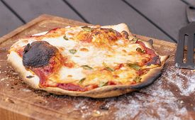 Homemade Pizza On A Wooden Board With Melted Cheese And Delicious Spices