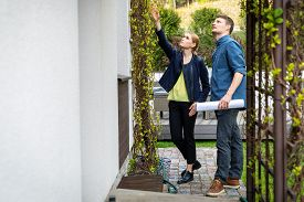 Real Estate Agent Presenting House To Customer Outdoors