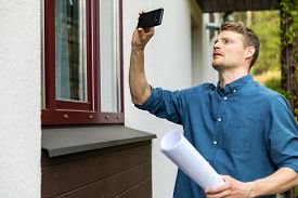 Real Estate Appraiser Taking Pictures Of Property With Phone