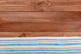 Top View On A Dark Wooden Table With A Linen Kitchen Towel Or Textile Napkin. A Tablecloth On A Coun