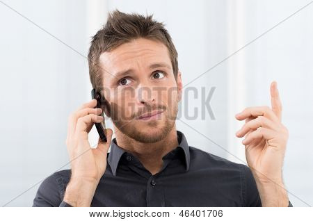 Businessman Listening Seriously On Mobile Phone In Office
