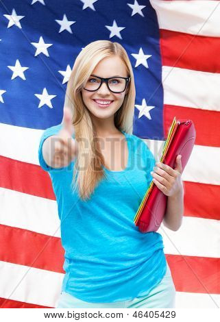student with folders showing thumbs up over american flag
