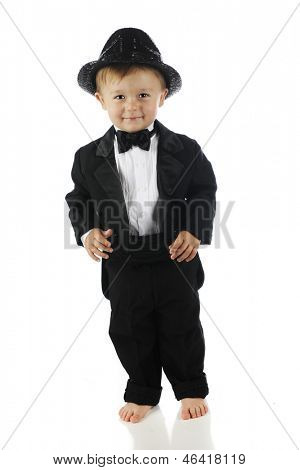 An adorable barefoot toddler happily dressed up in a sparkly hat, black bow tie and tuxedo.