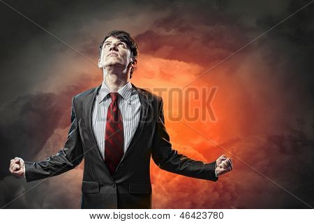businessman in anger with fists clenched looking in the sky