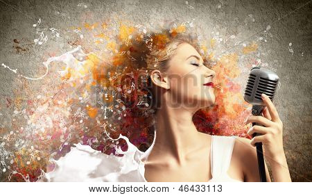 Image of female blonde singer holding microphone against color background with closed eyes