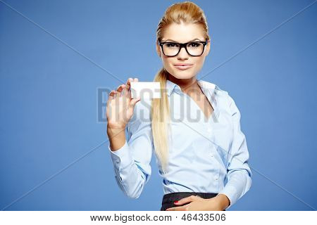 Businesswoman holding credit card. Isolated on blue