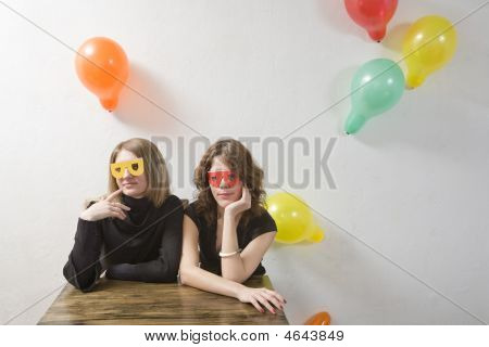 Two  Woman Wearing Funny Glasses Sitting At The Table