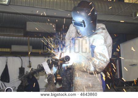 Labourer Arc Welding A Sheet Or Piece Of Metal