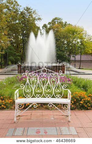 Decorative Bench In Autumn Park With Fountain