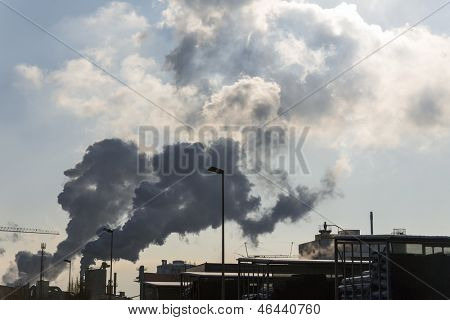an industrial plant chimney with smoke. symbolic photo for environmental protection and ozone.