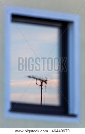 an antenna for a television set is reflected in the window of a house