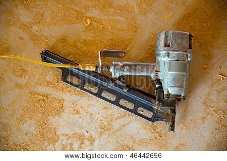 Air nail gun pneumatic framing nailer on grunge sawdust floor while house construction