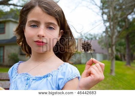 girl portrait with american sweetgum spiked fruit on park