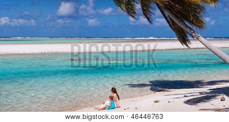 Beautiful mother and daughter on a deserted tropical beach