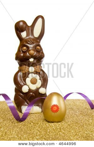 Easter Chocolate Bunny With Golden Egg Over White