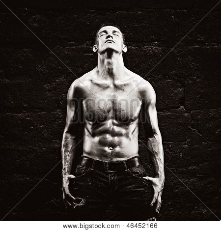Beautiful young strong man posing on dark background poster