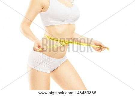 Attractive woman in white cotton underwear measuring her waist, isolated against white background