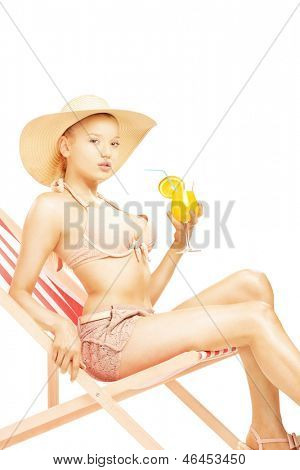 Attractive blond female with hat sitting on a sun lounger and drinking a cocktail, isolated on white background