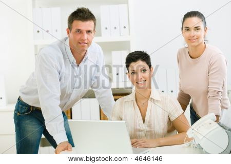 Team of happy office people working on laptop computer. poster