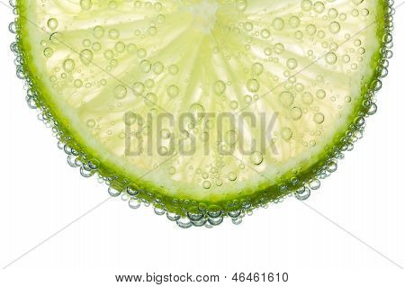 Lime Slice In Clear Fizzy Water Bubble Background