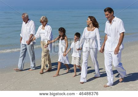 A happy family of grandparents, mother, father and two children, son and daughter, walking holding hands and having fun in the sand of a sunny beach