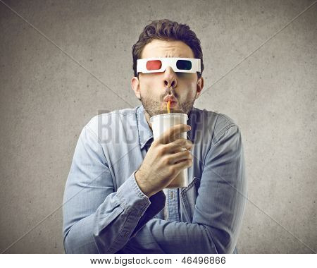 amazed man with 3D glasses watches movies while drinking