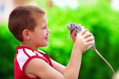 teenage boy playing with rat pet, outdoors poster