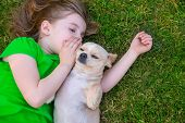Blond happy girl with her chihuahua doggy portrait lying on lawn poster