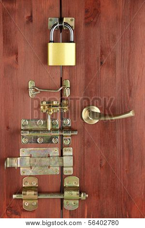 Metal bolts, latches and hooks in wooden door close-up poster