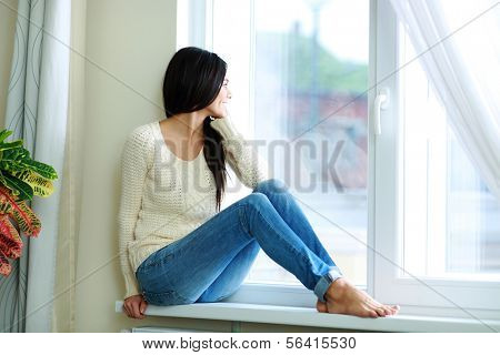 Young happy woman sitting on a window-sill and looking outside
