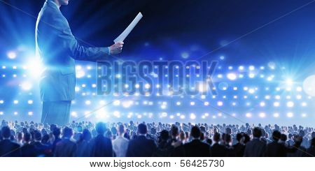 Back view of businessman speaker standing on podium in lights