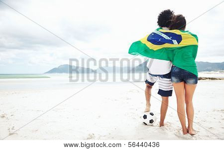 Brazil soccer fans stand on beach together with flag for world cup with ball