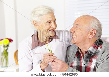 Happy senior citizen giving a freesia flower to smiling woman